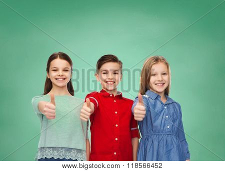 education, school, friendship, gesture and people concept - happy smiling children showing thumbs up over green chalk board background