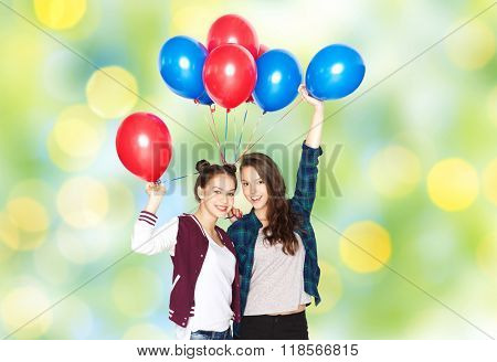 people, friends, teens, holidays and party concept - happy smiling pretty teenage girls with helium balloons over green summer lights background