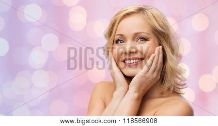 beauty, people and skincare concept - smiling woman with bare shoulders touching face over pink lights background
