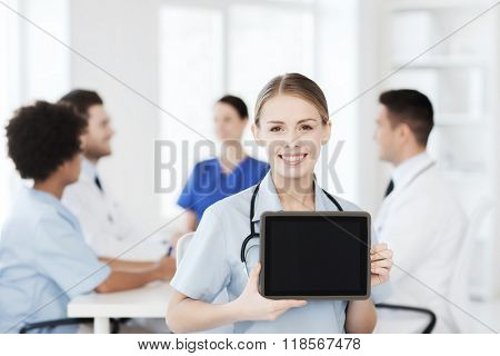 clinic, profession, people and medicine concept - happy female doctor showing tablet pc computer blank screen over group of medics meeting at hospital