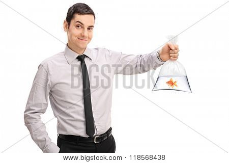 Studio shot of a young man holding a goldfish in a plastic bag filled with water isolated on white background