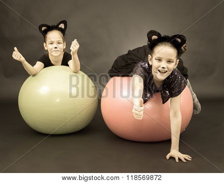Two Girls In Cat Costumes On Fitness Balls On Black Background In Vintage Style.
