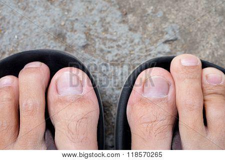 Feet Of Men Wearing Black Sandals On The Cement Floor.