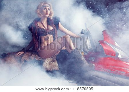 Woman posing on snowmobile