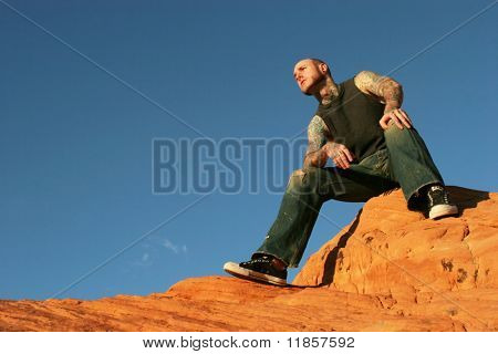 Tattoo man sitting on red rocks