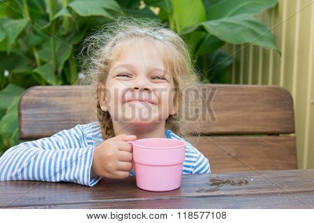 Four-year Girl Hamming Sitting At A Table With A Glass Of Juice