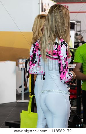 Blonde Promotional Models In Trade Show: Rear View