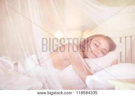 Gentle female sleeping in the bedroom under canopy, with pleasure relaxing in luxury spa resort, enjoying, calmness and harmony