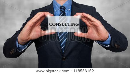 Businessman Holds White Card With Consulting Sign, Grey - Stock Photo