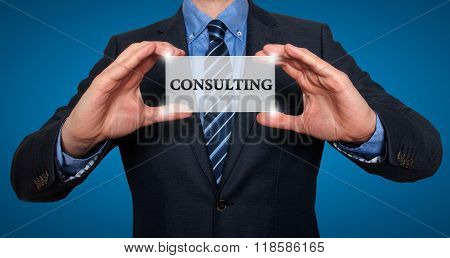 Businessman Holds White Card With Consulting Sign, Blue - Stock Photo