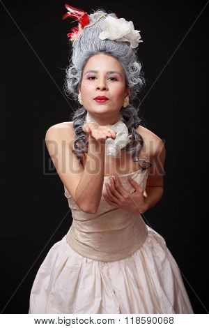 Portrait Of A Young Tender Woman In Crinoline Dress  Sending Air Kiss, Playful Expression