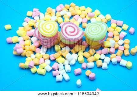 Colorful spiral jelly and colorful marshmallows on blue background. Focus on jelly.