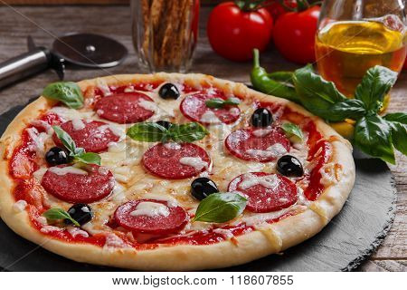 pizza with salami tomato and cheese on a black stone