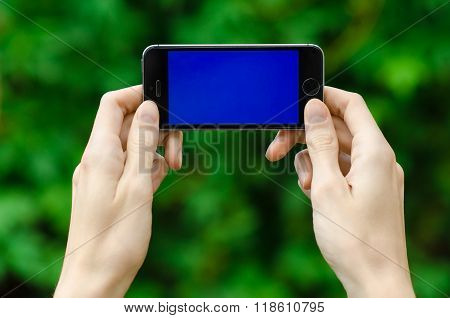Human Hand Holding A Modern Mobile Phone With A Blue Screen On A Background Of Green Grass First-per