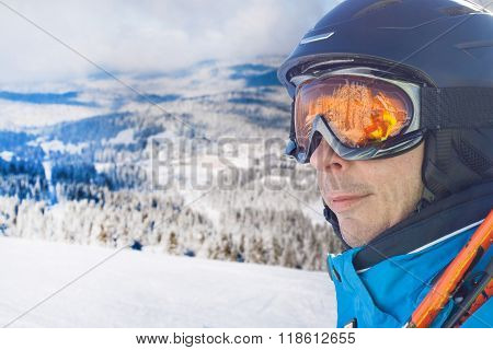 Skier man in the blue skiing jacket, helmet and glasses against snow forest panorama