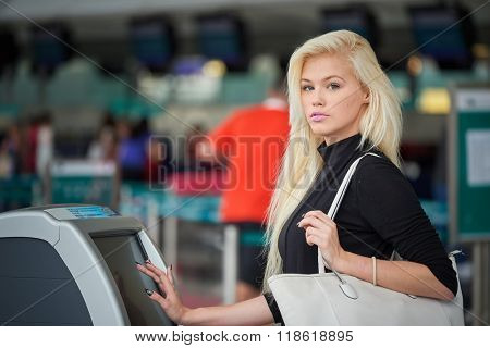 Blonde woman using self check-in kiosk in the airport