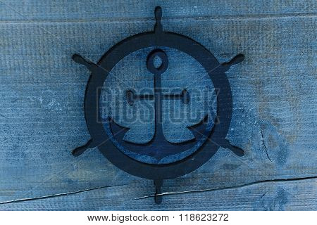 Blue Anchor And Rudder Icon Carved In The Wood, Texture For Nautical Design.