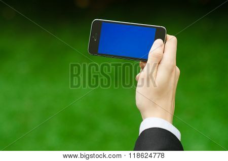 Communication And Business Subject: Hand In A Black Suit Holding A Modern Phone With Blue Screen In