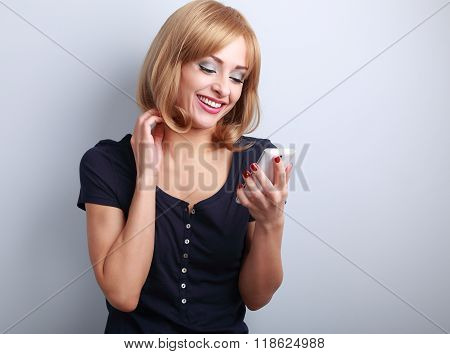 Happy Smiling Blond Woman Chating In Mobile Phote On Blue Background