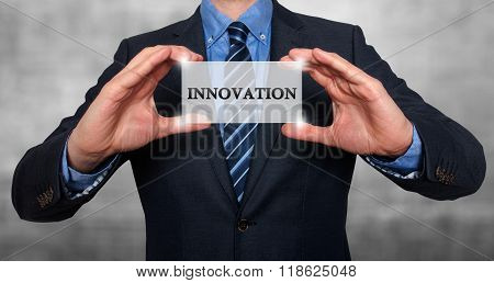 Businessman Holding White Card With Innovation Sign, Grey - Stock Photo