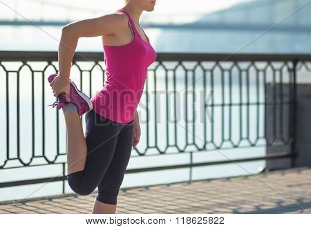 Sport woman doing stretching outside in city quay
