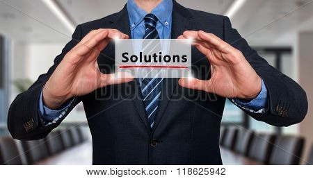 Businessman Holding White Card With Solutions Sign, Office - Stock Photo