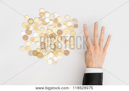 Money And Finance Topic: Money Coins And Human Hand In Black Suit Showing Gesture