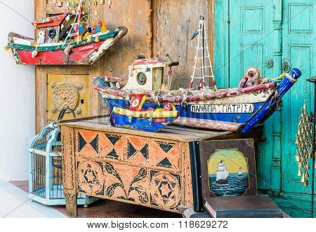 OIA, SANTORINI, GREECE - AUGUST 2015: Wooden color souvenirs of fishing boats as decoration of wall in Oia town on Santorini island. Oia is the most popular city on Santorini island.