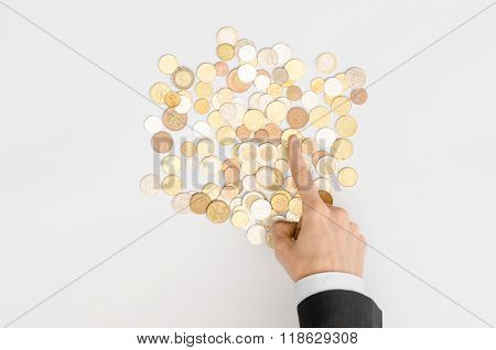 Money And Finance Topic: Money Coins And Human Hand In Black Suit Showing Gesture On A Gray Backgrou