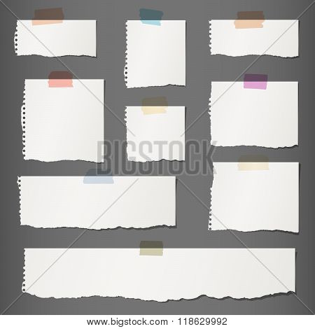 Pieces of torn white blank note paper with colorful sticky tape on dark gray background