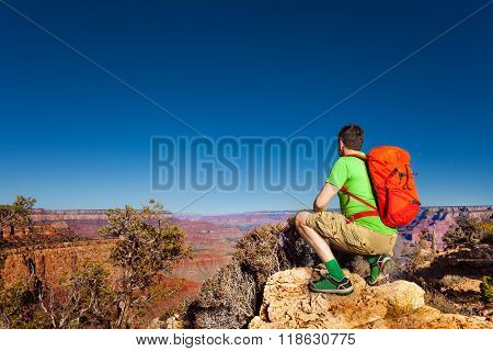 Young man look at grand Canyon sit on squads