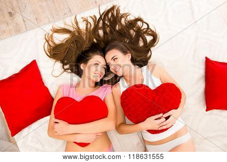 Cheerful Beautiful Girls In Pajamas Lying On The Bed Holding Pillows