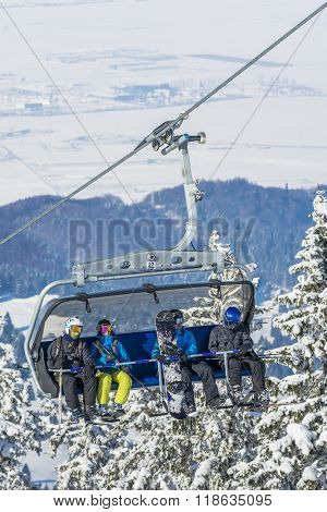 Tourists In Chairlift In Winter Season