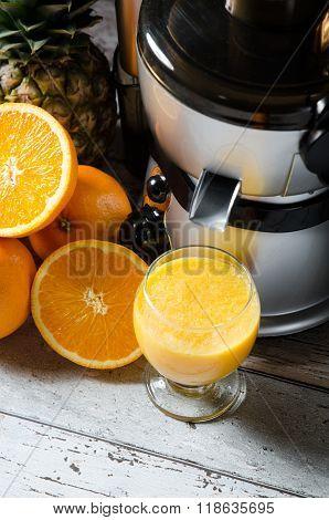 Juicer And Orange Juice In Glass On Wooden Desk
