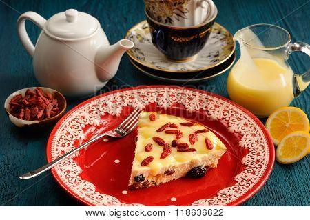 Yummy Homemade Cheesecake With Raisins, Lemon Curd And Goji Berries On Red Plate
