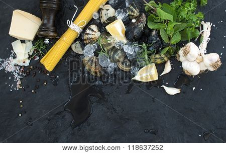 Ingredients for cooking Spaghetti vongole. Clams on chipped ice, raw pasta, Parmesan cheese, garlic,