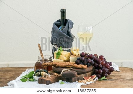 Glass of white wine, cheese board, grapes, fig, strawberries, honey and bread sticks  on rustic wood