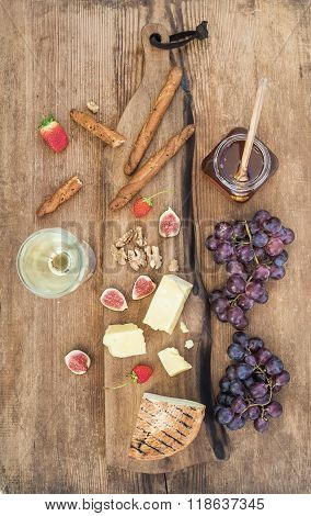 Glass of white wine, cheese board, grapes, figs, strawberries, honey and bread sticks on rustic wood