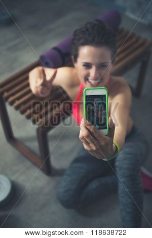 Closeup On Fitness Woman Sitting In Loft Gym And Taking Selfies