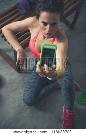 Fitness Woman Sitting In Loft Gym And Taking Selfies