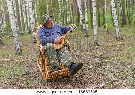 Senior man is having rest in birch forest sitting on a wicker rocking-chair