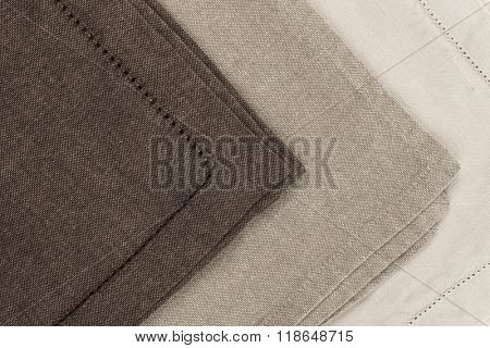 Edges of linen cloth napkins in brown and beige natural colors close up