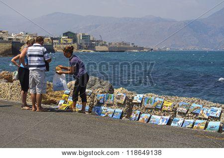 HERAKLION, CRETE, GREECE - AUGUST 15, 2013: People buy souvenirs near Heraklion coastline. Heraklion is the capital city of Crete island, Greece