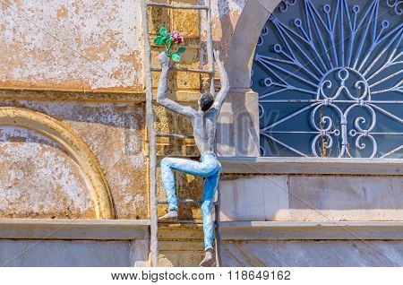 OIA, SANTORINI, GREECE - AUGUST  15, 2013: Sculpture of climbing men as decoration of old building in Oia town, Santorini island Oia is a very popular city among tourists on Santorini island