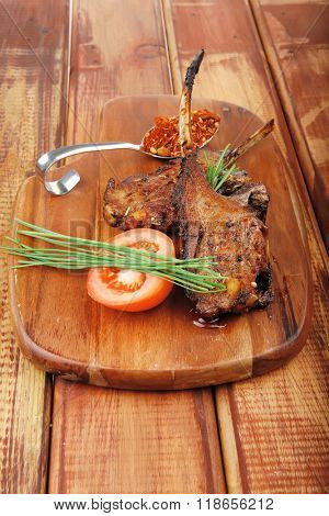 meat on wooden plate : roast ribs on wood with tomatoes chives and dry spices over wooden table