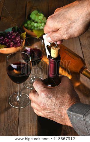 Closeup of a man opening a wine bottle.