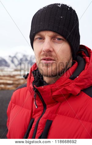 Portrait of outdoors sporty rugged adventure man with puffy jacket and beanie, in cold extreme winter weather
