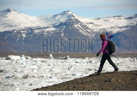 Woman traveller hiking around Jokulsarlon glacier Lagoon with iceland flag flying in the wind
