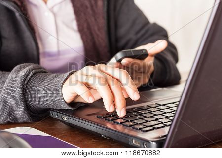 Woman Using Smart Phone At Office Desk