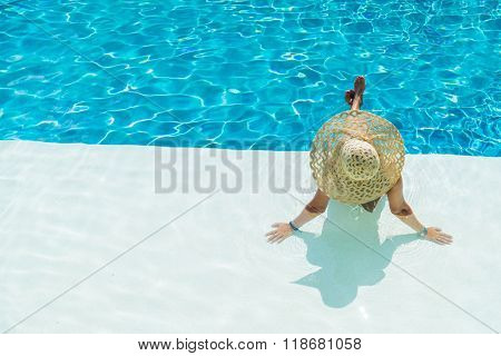 Young woman sitting on the ledge of the swimming pool.
